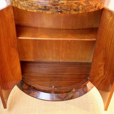 An Art Deco demi-lune cocktail cabinet by Harry and Lou Epstein.  Figured walnut veneers, with mirrored, lit, glass shelved  interior to top. Mahogany lined, shelved cabinet to base. H 168cm, W 91cm, D 48cm. English, ca. 1930 (hva)
