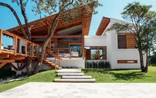 Casa incorpora arvore ao deck e aproveita a sombra.