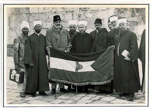 Hajj Amin (center) presenting Palestinian flag to Mawlana Shawkat Ali, (left of Hajj Amin) a leader of Indian Khilafat movement; next to Shawkat Ali is Shaykh Khwaja Nazir Hasan Ansari, 1931. © Ahmad al-Ansari.