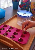 Use tongs to transfer themed objects from an ice cube tray to a container with a small hole in the lid.