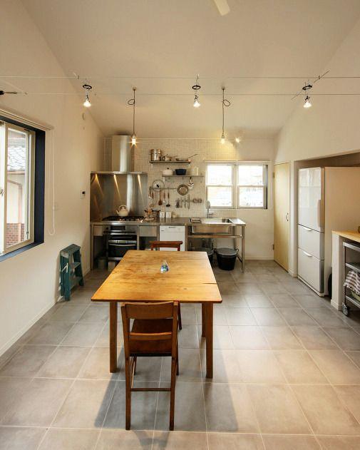 グレーのタイル貼りの床や厨房のようなステンレス仕上げのキッチンが