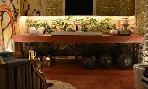 Para sair do convencional, Carla Marques optou por não colocar pontos de iluminação no teto, algumas lâmpadas dicróicas estão no chão dando efeito nas paredes, atrás do espelho foi usada uma fita de led laranja.