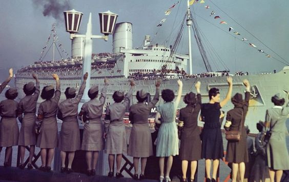 This photo from June 17th 1945 shows men of the 86th Infantry Division of the third Army arriving back to the United States at the end of WWII. They stand on the deck cheering as the women on the dock wave to them, awaiting their arrival.