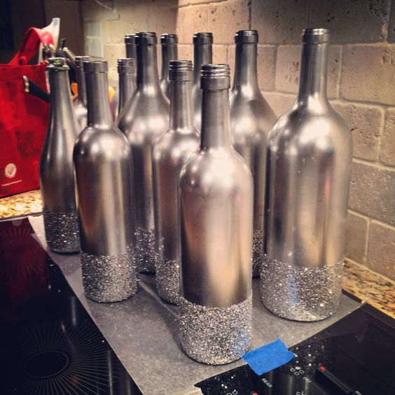 Variety of different size Wine bottles, spray painted metallic silver, with silver glitter glued to the base for my vases that go on my bistro tables at Tyler's 2014 Cattle Barons' Gala.