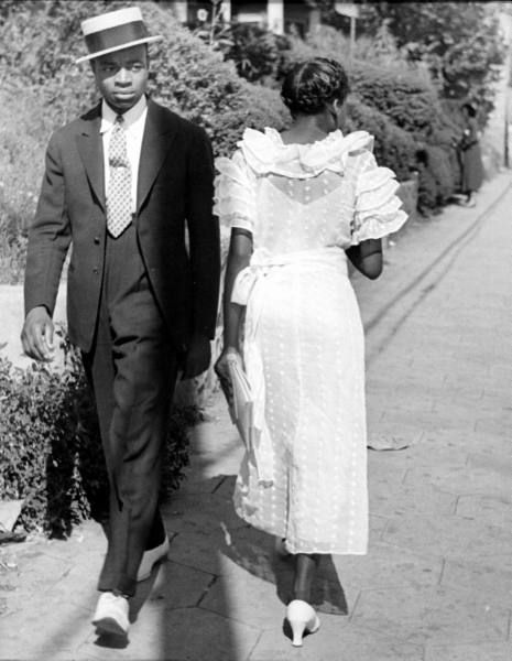 Young gentleman in his Sunday finery glances at a young woman in a ruffled dotted-swiss dress, as she passes him on the street. Mississippi, 1937, photo by Alfred Eisenstaedt
