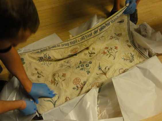 Carefully unpacking the beautiful Morris bed cover.     Photo © Simon Harvey Williams, Crown Fine Art  with thanks to www.sal.org.uk