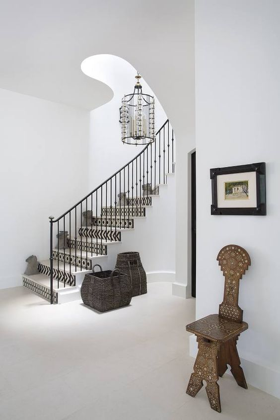 rustic entry with all white walls and floors and ceiling, mosaic staircase, black wrought iron staircase