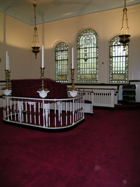 Shearith Israel - New York City, New York - Little Synagogue -   The Sabbath lamp hanging in front of the west window is from the first Mill Street Synagogue, and the bench under the windows on the west wall is from the Crosby Street Synagogue (1834).