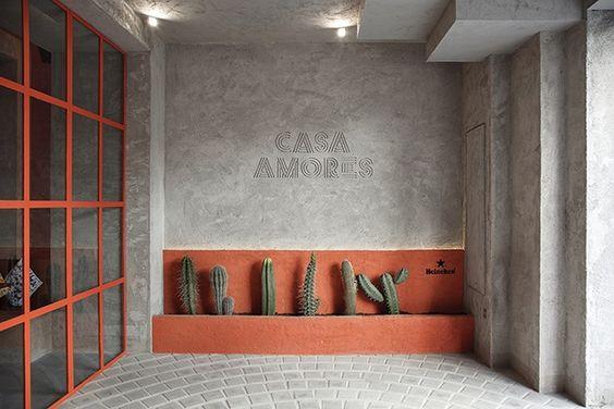 Patio de entrada con una calzada pavimentado con adoquines de cemento formando una espiral. Típicos cáctus decoran el espacio con tonos naranjas en la pared y en la cristalera de acceso al local.