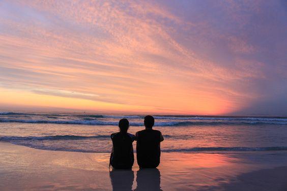 Casal na praia vendo o pôr do sol.