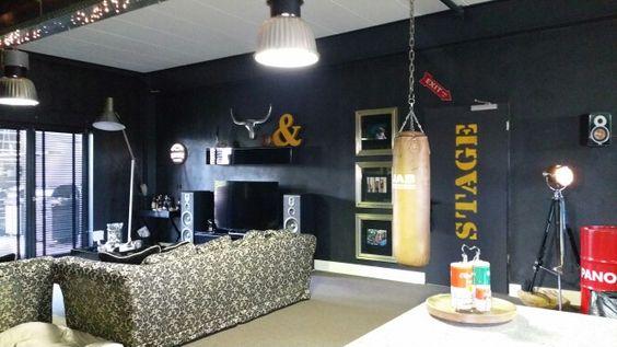 Wohnzimmergestaltung. Coole schwarze Wände mit ein paar Accessoires im Loft-Style und roten und gelben Akzenten.