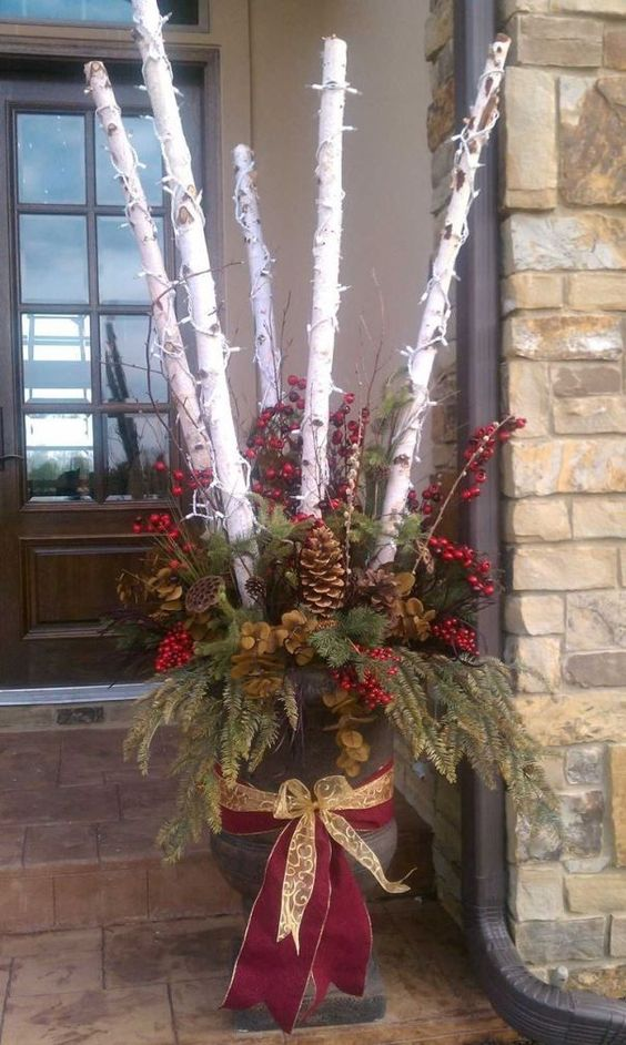 flower pt wrap with a a red ribbon and tree branches sticking out wrapped with Christmas lights #christmas  #containers #planters #gardenplanters #Log #birch  #christmasLights #pinecones