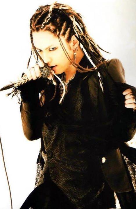 三つ編みスタイルで黒い衣装を着て歌うL'Arc〜en〜Ciel・hydeの画像