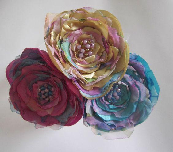 Kit com 3 palitos de cabelo em acrílico com flores de cetim em tons de rosa magenta, azul e bege e camadas de chiffon. Podem ser usados juntos em um penteado ou separadamente em coques de cabelo, etc. diâmetro de cada flor: aproximadamente 8 cm.
