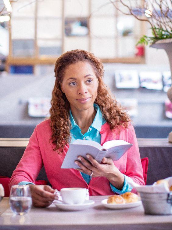 Uma mulher segura a Bíblia aberta e olha para frente com confiança