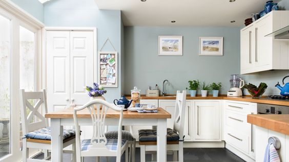 In this large family kitchen, the white units and wooden worktops are classic country and are mirrored brilliantly in the design of the table and dining chairs. Artwork featuring coastal views and accessories in various shades of blue and teal are reminiscent of the ocean, adding a seaside twist to the room and cleverly playing off the wall colour