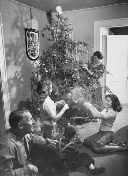 Happy times! A family decorates their tree with plenty of crinkled silver icicles (1953). ~~~~ (retro, vintage, yesteryear, Xmas, holidays)