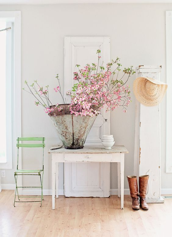 Spring inspiration, decorating ideas, and interior design! Pink flowering branches in a French zinc vase on a farm table. Spring green French bistro or cafe chair in white vignette by Dreamywhites.