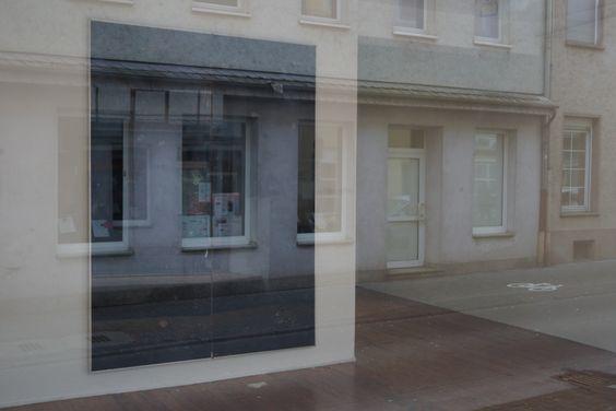 Blick durch das Fenster der Galerie Junge Kunst Trier in den Schwarzspiegel aus der Ausstellung NEURO von Sebastian Böhm und wieder zurück auf die Karl-Marx-Straße