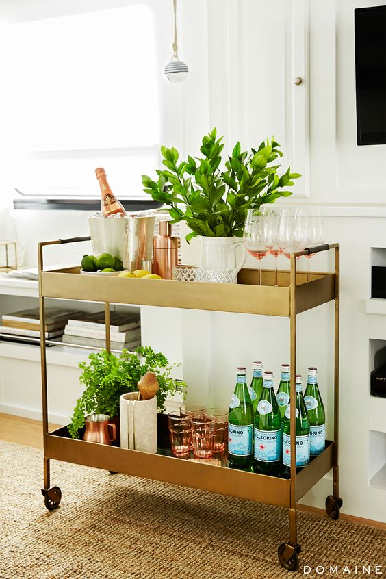 Gold bar cart with rose gold accessories and plants