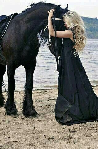 Friesian Black Stallion on the beach with his head bowed down snuggling and nuzzling with his girl in a hug. Lady has beautiful long black dress on. Horse looks so sweet. Stunning horse photography.