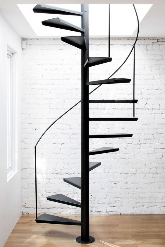 A blackened steel staircase allows access to a wood decked for Square spiral staircase plans hall