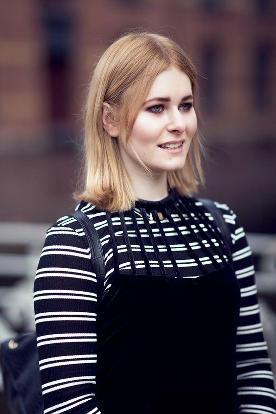 Christina Key lächelt in die Ferne und trägt ein schwarz-weiß gestreiftes Shirt und darüber ein edles Kleid