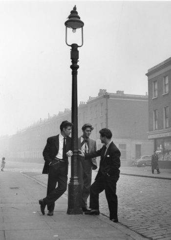 Cosh Boys in Notting Hill, London in 1954 wearing finger-tip length jackets of a style which immediately preceded Teddy Boy style. Note the chain attached to the belt loop, which was a direct influence from the Zoot Suit.  Following on from the Spivs and during the early 1950's some teenage gangs started to appear in the East End of London and they became known as Cosh Boys.