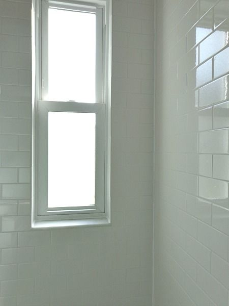 1940's subway tile shower with a window