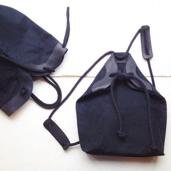 CANVAS zwart inimal rugzak met lederen details Het canvas is waterafstotend Het zwarte touw is zacht en dik.  binnen: sleutelhanger 1 binnenzakje  afmetingen ±: w. 27cm x h.40cm x d.10cm - - - - - - - - - - - - - - - - - - - - - - - - - - - - - - - - - - - - - - - - - - - - - - - - = dit is een made to order product = + kleuren kunnen varieren van scherm tot scherm +