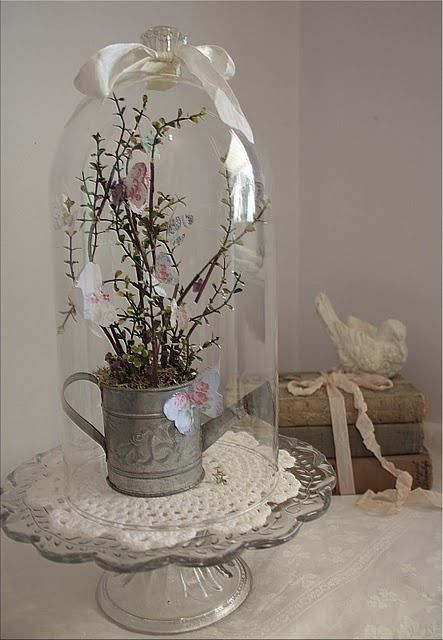 Look how great this old watering can looks when you place it under glass and add some dried flowers, and a ribbon.