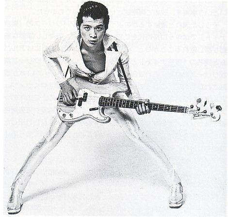 上下白い衣装を着てギターを持っている昔の矢沢永吉の画像