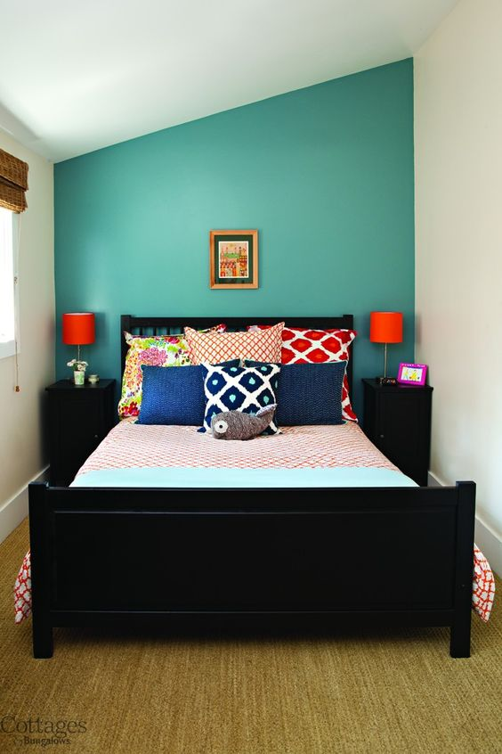 Small Cottage Guest Bedroom With Lots Of Bright Accents Pillows And Accent Wall Home Design