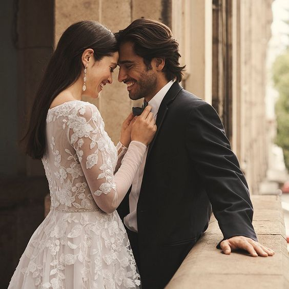 These romantic moments between the newlyweds 💕 We can't help but swoon over this alluring wedding dress, with its illusion sleeves and bodice and plunging neckline. Shop this lace ball gown wedding dress from the Galina Signature collection exclusively at David's Bridal