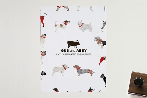 """The 2015 Dog Calendar features 12 unique dog illustrations. Showcase each month by adding this fun item to any magnetic surface. There is a glue adhesive strip at the top of each calendar allowing you to """"tear-off"""" each month, too!"""