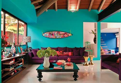 O azul-turquesa (Lukscolor, ref. LKS 1915*) cobre a parede da sala e faz uma bela parceria com o roxo berinjela dos sofás (Micasa). Da mesma loja veio a mesa de centro. Atrás do estofado, prancha de surfe pintada por Isabelle Tuchband.:
