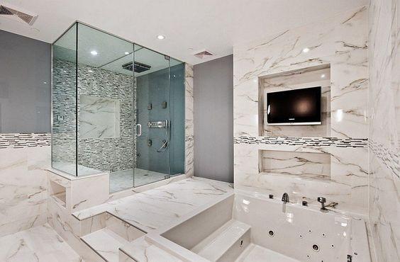salle de bain de luxe avec un carrelage mural et de sol en marbre blanc, une…