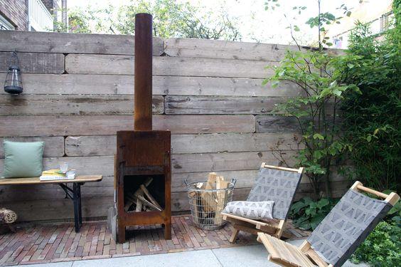 Sfeer volle tuinhaard tegen steigerhouten schutting. Tuin is ontworpen en aangelegd door hoveniersbedrijf van Elsäcker Tuin