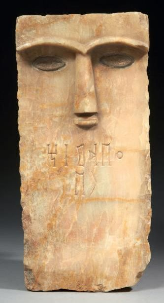 STELE ICONIC. Rectangular stele carved with a stylized face face. Thin, straight nose, surmounted by eyebrows in high relief, is framed by blue glass inlaid eyes. It is engraved with two lines in South Arabian characters: owner's name. Alabaster and inlaid blue glass paste. South Arabian Peninsula, ca. Third-first centuries BC.