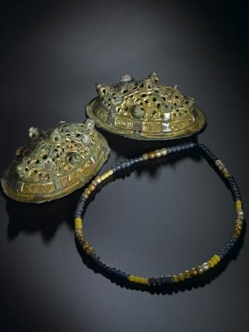 Double-shelled oval brooch of gilt bronze, ornamented with zoomorphic designs, and blue glass bead with two segments from a Viking grave group from Kneep Head, Valtos, Uig, Isle of Lewis, 900 - 1000