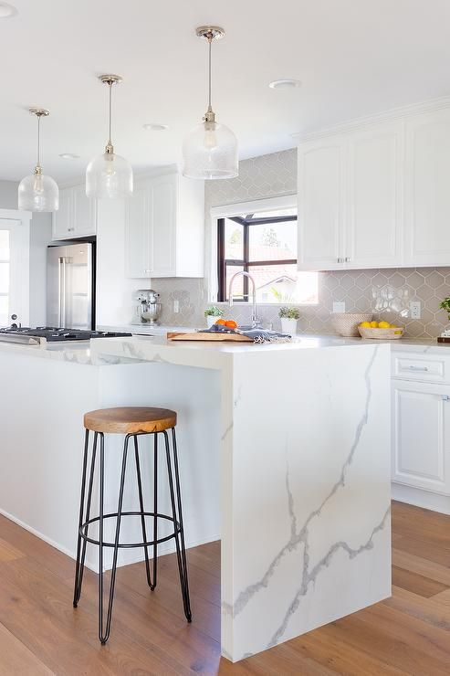 Extended Kitchen Island With A Marble Like Quartz Waterfall Countertop Extends From A White Island Fea Waterfall Countertop Waterfall Island Kitchen Home Decor