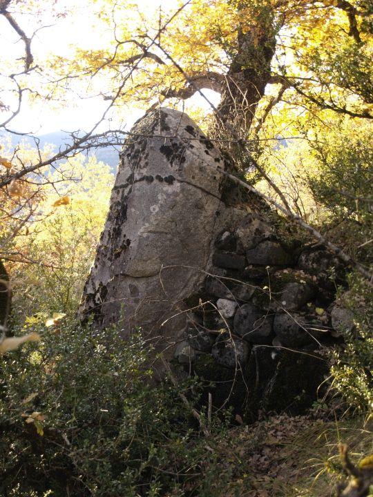 Menhir-muga entre cuatro campos o fajas antiguas de cultivo. se encuentra respaldada con el mismo muro de piedra seca.