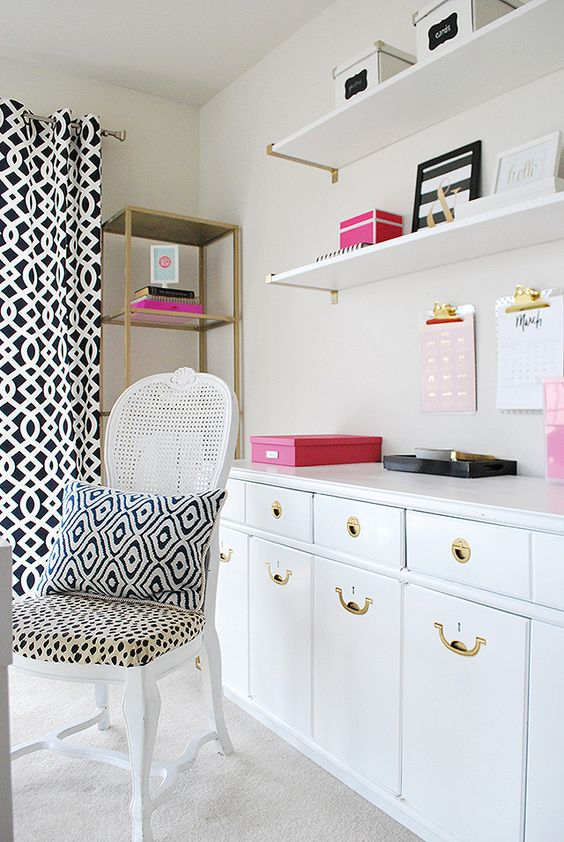 "A fun print on a chair, a cute pillow and fun pops of pink dress up an otherwise ""white"" home office. Using the wall expands storage space--clipboards with calendars hang, the shelves contain boxes of office supplies and a credenza keeps files to create an organized and colorful workspace. Sponsored Pin."