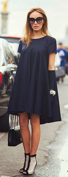 An example of a Tent Dress City Style- A tent dress is a dress that hangs loose from the shoulder to below the hips, and does not have a waistline. Typically it is worn without a belt or elastic so that it can hang loosely.