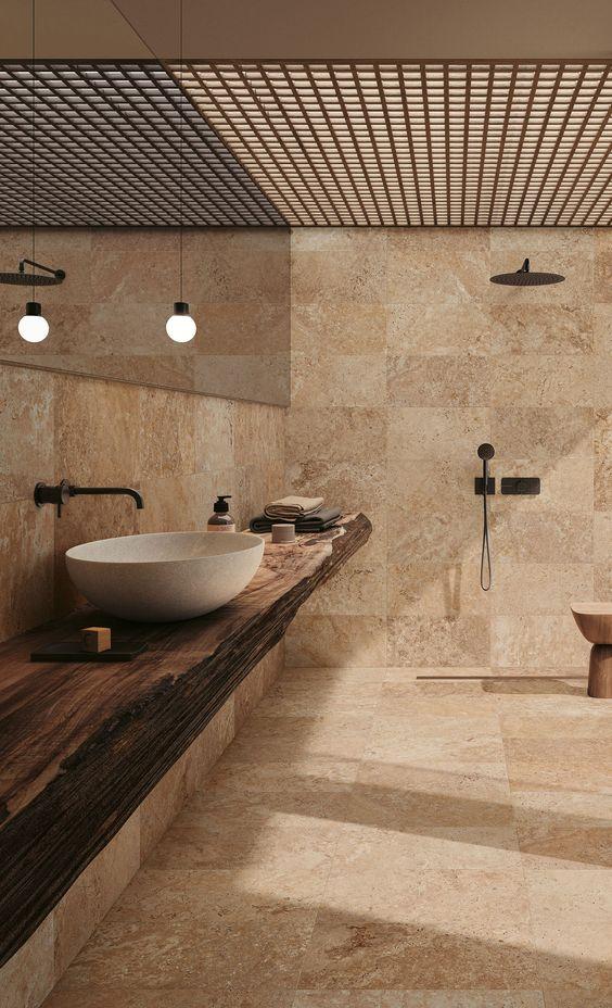 Skapa ett lugnt och omfamnande badrum genom att välja klinker i jordnära toner och kombinera med till exempel trädetaljer.