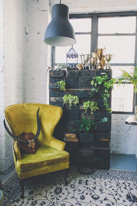 Sillón de terciopelo amarillo y decoración industrial.