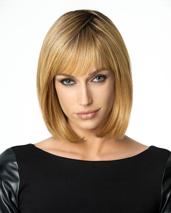 Classic Page Synthetic Wig by Hair Do  This blunt cut, to-the-shoulder length page includes an undefined, left of center part with soft, full bangs and expertly tapered sides that angle up to a slightly shorter back.