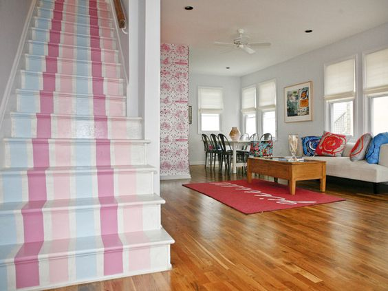 These bright, cheerful vertical stripes coordinate with the pink and blue hues featured in this eclectic living room, while also leading the eye upstairs. Design by Cortney and Robert Novogratz.
