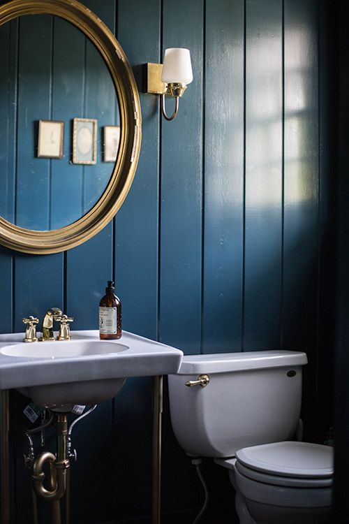 Dark blue walls and gold accents in the bathroom
