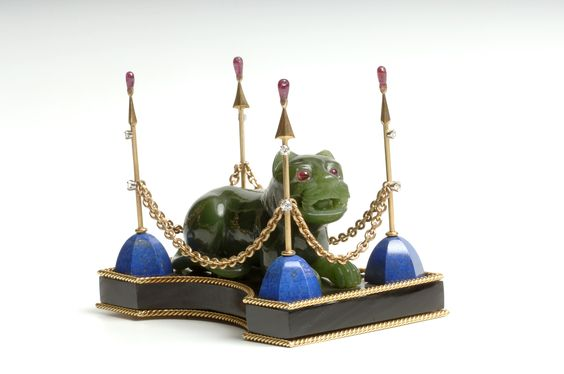 BLack Obsidian base is framed top and bottom with 18 karat yellow gold wire ( 2.1 mm thick). On top of base is a lion with ruby eyes carved from nephrite jade. At each corner of the base is a pole containing two diamonds. The base of the pole is lapis, the shaft is 18 karat yellow gold, and the finial is a pear shaped ruby bead glued into a four prong setting. The poles are connected with an 18 karat yellow gold link chain. Marks: Designed by George Headley 1971. David Webb 18K